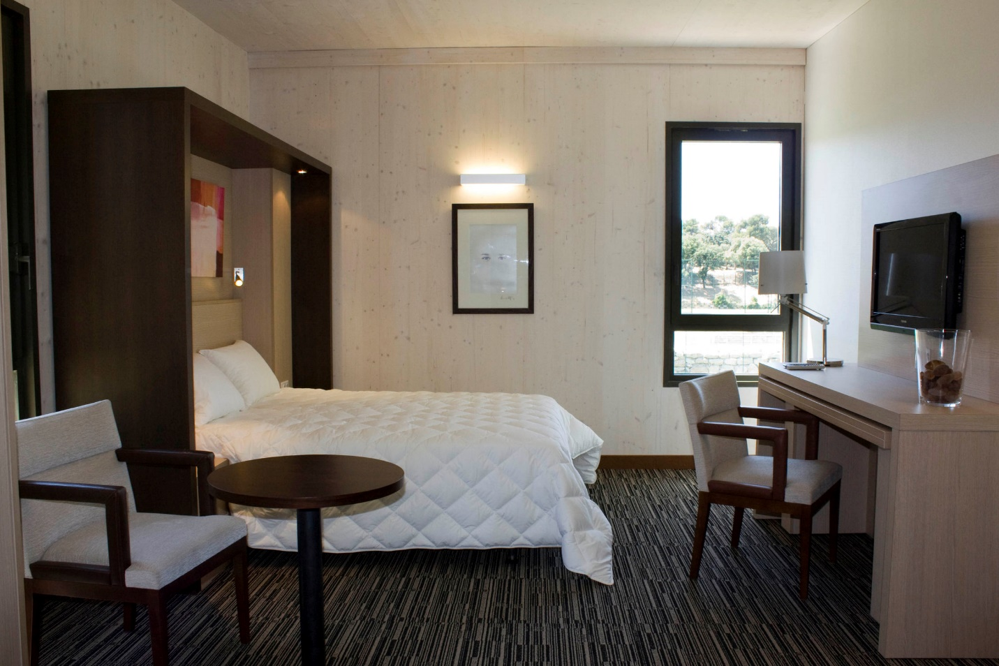 Hotel Room with small-scale furniture and pull-out desk to make it feel larger